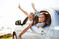 Счастливые девочка-подростки или женщины в автомобиле на взморье Стоковое Фото