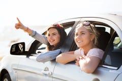 Счастливые девочка-подростки или женщины в автомобиле на взморье Стоковые Фотографии RF