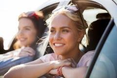 Счастливые девочка-подростки или женщины в автомобиле на взморье Стоковые Фото