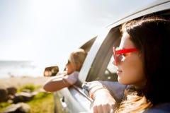 Счастливые девочка-подростки или женщины в автомобиле на взморье Стоковая Фотография RF