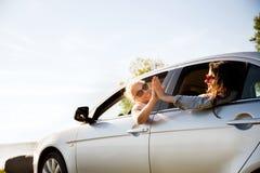 Счастливые девочка-подростки или женщины в автомобиле на взморье Стоковые Изображения RF