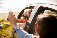 Счастливые девочка-подростки или женщины в автомобиле на взморье Стоковое Изображение RF