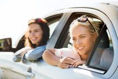 Счастливые девочка-подростки или женщины в автомобиле на взморье Стоковая Фотография