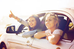 Счастливые девочка-подростки или женщины в автомобиле на взморье Стоковое фото RF