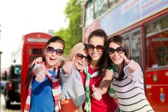 Счастливые девочка-подростки или женщины показывая большие пальцы руки вверх Стоковые Изображения RF