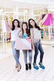 Счастливые девочка-подростки нося хозяйственные сумки стоковые изображения