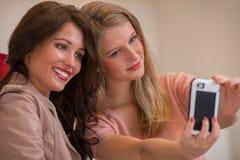 Счастливые девушки внутри помещения фотографируя пока ходящ по магазинам Стоковые Изображения