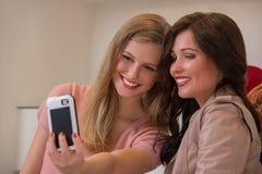 Счастливые девушки внутри помещения фотографируя selfie пока ходящ по магазинам Стоковое Изображение