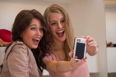 Счастливые девушки внутри помещения фотографируя selfie пока ходящ по магазинам Стоковая Фотография