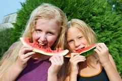 Счастливые девушки есть арбуз Стоковые Изображения RF