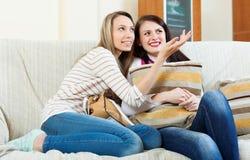 Счастливые девушки злословя на софе Стоковая Фотография RF
