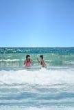 Счастливые девушки играя в красивом океане Стоковая Фотография