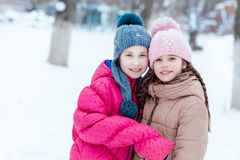 Счастливые девушки играя на снеге в зиме Стоковое фото RF