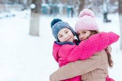 Счастливые девушки играя на снеге в зиме Стоковые Изображения RF