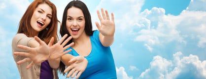 Счастливые девушки или молодые женщины показывая их ладони Стоковые Изображения RF