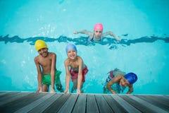 Счастливые девушки и мальчики плавая в бассейне Стоковая Фотография RF
