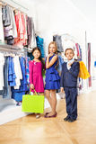 Счастливые девушки и мальчик с красочными хозяйственными сумками Стоковые Изображения