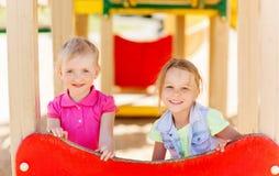 Счастливые девушки на спортивной площадке детей Стоковое Изображение