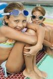 Счастливые 2 девушки нося изумлённые взгляды заплыва бассейном Стоковые Изображения RF