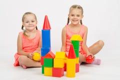Счастливые 2 девушки построили замок из блоков Стоковая Фотография