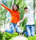 Счастливые девушки подростка скача оно парк Стоковое фото RF