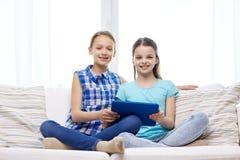 Счастливые девушки при ПК таблетки сидя на софе дома Стоковые Изображения RF