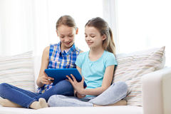 Счастливые девушки при ПК таблетки сидя на софе дома Стоковая Фотография RF