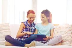 Счастливые девушки при ПК таблетки сидя на софе дома Стоковое Изображение