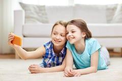 Счастливые девушки при smartphone принимая selfie дома Стоковое Изображение