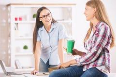 Счастливые девушки работая в офисе Стоковые Изображения RF