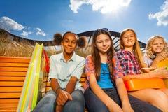 Счастливые девушки сидя вместе с хозяйственными сумками Стоковая Фотография