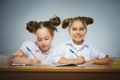 Счастливые девушки сидя на столе на серой предпосылке школа copyspace принципиальной схемы черных книг предпосылки Стоковое Фото