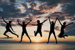 Счастливые девушки скача на пляж на времени захода солнца Стоковое Изображение RF