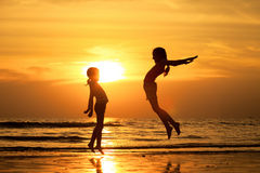 Счастливые девушки скача на пляж Стоковые Изображения
