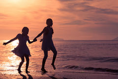 Счастливые девушки скача на пляж Стоковая Фотография