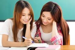 Счастливые девушки студентов наблюдая книги в классе стоковое фото