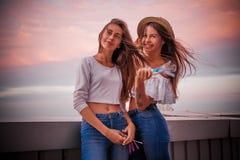 Счастливые девушки с сильным летанием волос в ветре Стоковые Фото