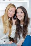 Счастливые девушки слушая к друзьям на телефоне Стоковые Изображения