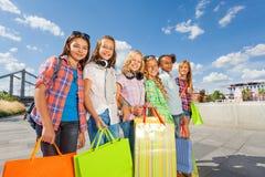 Счастливые девушки с хозяйственными сумками стоят совместно Стоковое Фото