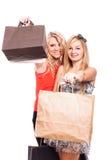 Счастливые девушки с хозяйственными сумками Стоковые Изображения