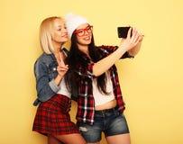 Счастливые девушки с smartphone над желтой предпосылкой Счастливая собственная личность Стоковое Изображение