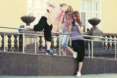 Счастливые девушки школы используя умный телефон в улице города Стоковые Изображения RF