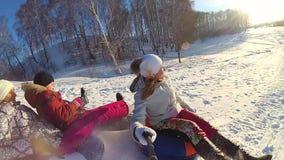 Счастливые езды семьи и усмехаясь snowtube на снежных дорогах движение медленное Ландшафт зимы снега Outdoors спорт Заход солнца сток-видео