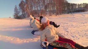 Счастливые езды семьи и усмехаясь snowtube на снежных дорогах движение медленное Ландшафт зимы снега Outdoors спорт Заход солнца видеоматериал