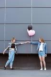 Счастливые лесбосские пары держа руки с воздушными шарами outdoors Стоковые Фотографии RF
