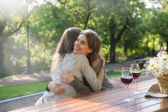 Счастливые детеныши 2 женщины сидя outdoors в вине парка выпивая Стоковые Фото