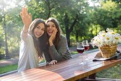 Счастливые детеныши 2 женщины сидя outdoors в вине парка выпивая Стоковое Изображение
