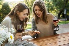 Счастливые детеныши 2 женщины сидя outdoors в вине парка выпивая Стоковые Фотографии RF