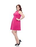 Счастливые детеныши плюс женщина размера представляя в розовом платье Стоковые Изображения
