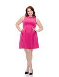 Счастливые детеныши плюс женщина размера представляя в розовом платье Стоковые Фото